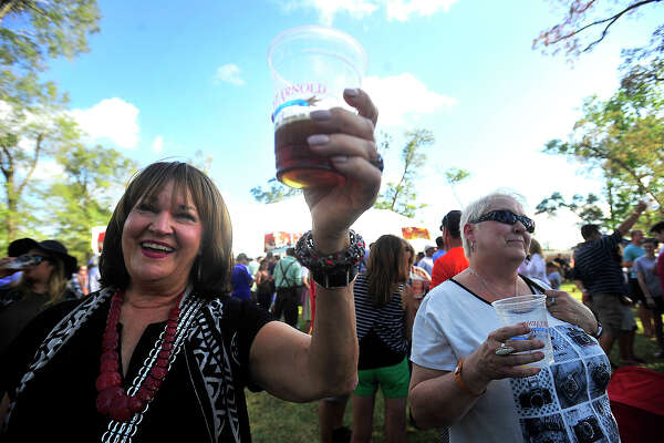 "Patricia Barry Rumble (left) and friend Diane Rogers join in a sing-along to ""Ein Prosit"" during Beaumont's second annual Oktoberfest event held Saturday at Rogers Park. Musical entertainment, including a polka performance by The Royal Klobasneks, food trucks, and a beer garden featuring regional craft beers rounded out the main events.  Photo taken Saturday, October 15, 2016 Kim Brent/The Enterprise"