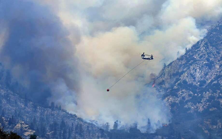 A helicopter flies past a section of a wildfire southwest of Split Mountain, above Wofford Heights, Calif., making a run to Isabella Lake to get a load of water before making another water drop Monday, Aug. 22, 2016. More than 10,000 firefighters battled wildfires Monday from California's Central Coast to Sierra Nevada forests or mopped up remnants of destructive blazes beaten into submission up and down the state. (Casey Christie/The Bakersfield Californian via AP) Photo: Casey Christie, Associated Press
