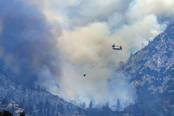 A helicopter flies past a section of a wildfire southwest of Split Mountain, above Wofford Heights, Calif., making a run to Isabella Lake to get a load of water before making another water drop Monday, Aug. 22, 2016. More than 10,000 firefighters battled wildfires Monday from California's Central Coast to Sierra Nevada forests or mopped up remnants of destructive blazes beaten into submission up and down the state. (Casey Christie/The Bakersfield Californian via AP)