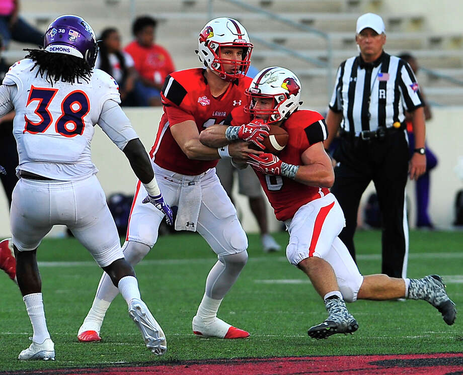 Lamar's Carson Earp hands off the ball to Kade Harrington as they pick up yards against Northwestern State during Saturday's home match-up at Provost-Umphrey Stadium. Photo taken Saturday, October 15, 2016 Kim Brent/The Enterprise Photo: Kim Brent / Beaumont Enterprise