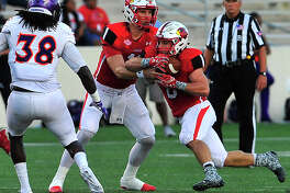 Lamar's Carson Earp hands off the ball to Kade Harrington as they pick up yards against Northwestern State during Saturday's home match-up at Provost-Umphrey Stadium. Photo taken Saturday, October 15, 2016 Kim Brent/The Enterprise