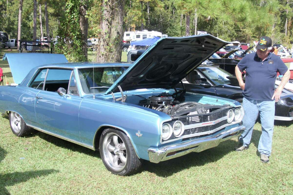 A visitor at the Wolf Creek Car Show is distracted by the sight of a 1965 Chevrolet Chevelle owned by Wayne Wells.
