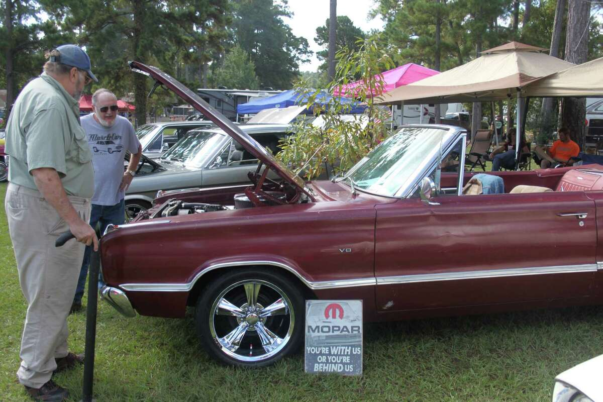 A 1967 Dodge Coronet owned by Thomas Capps catches the eyes of two spectators at the Wolf Creek Car Show.