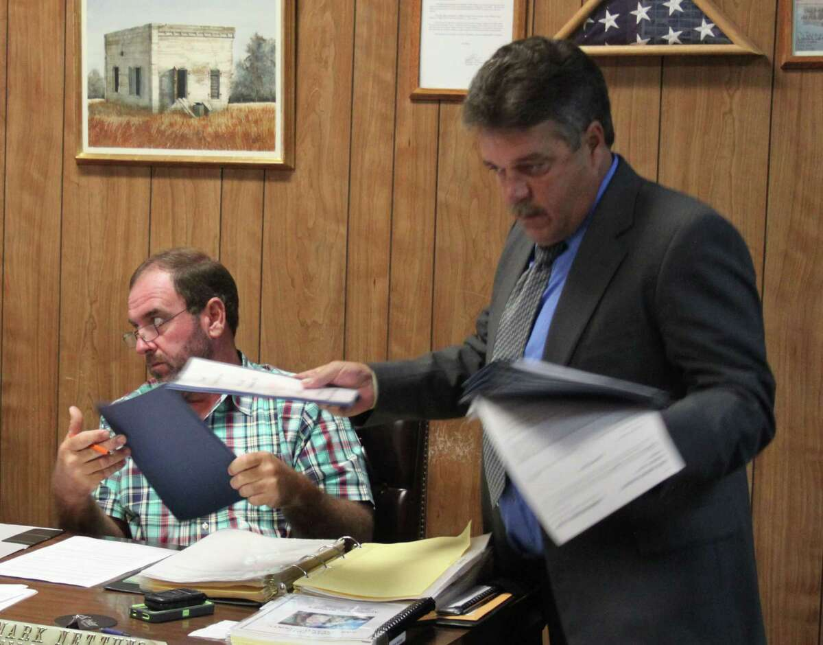 Donald McClure (right) of Texas Auto Title and Registration Consultants passes out information on how his company can benefit San Jacinto County with its Abandoned, Forfeiture and Impounded Vehicle program.