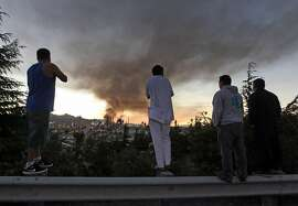 Spectators view the fire at the Chevron Oil refinery from the top of a guardrail as the fire fills the sky with black smoke above Richmond Calif, Monday August 6, 2012.