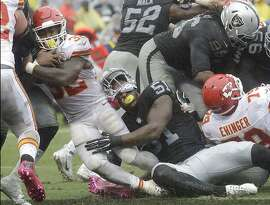 Kansas City Chiefs running back Spencer Ware (32) runs for a touchdown past Oakland Raiders outside linebacker Bruce Irvin (51) during the first half of an NFL football game in Oakland, Calif., Sunday, Oct. 16, 2016. (AP Photo/Marcio Jose Sanchez)