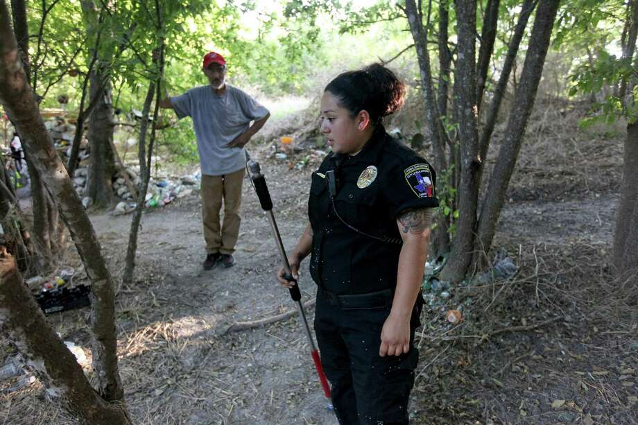 Luis Lopez talks with ACS Officer Sabrina Oyervides about roaming dogs that live in a patch of woods on the West Side. Animal experts estimate that only 1 out of every 5 roaming dogs in the city can be considered truly homeless. Photo: Edward A. Ornelas /San Antonio Express-News / © 2016 San Antonio Express-News