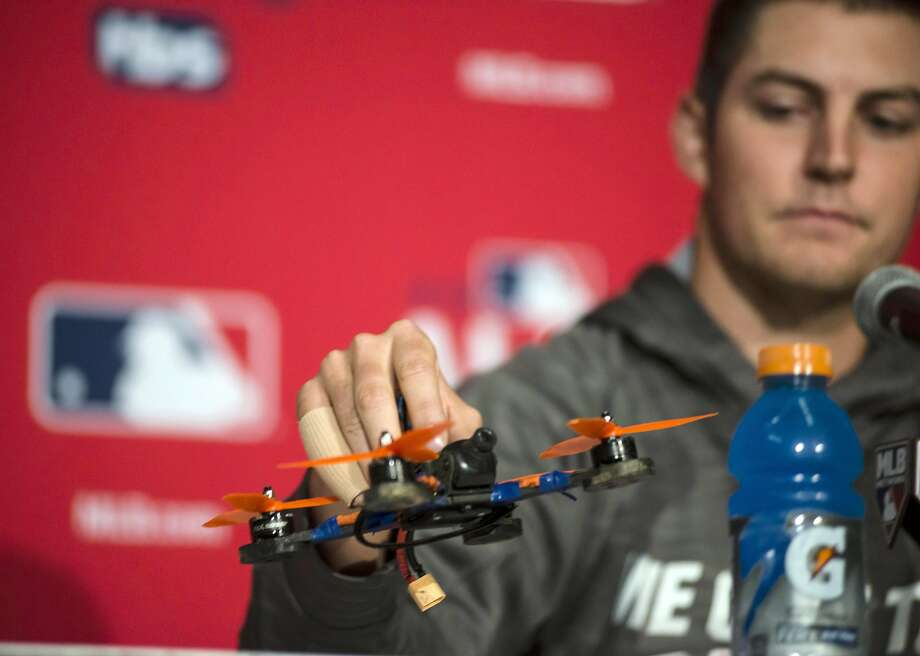 Cleveland pitcher Trevor Bauer introduces the drone that cut his finger at a news conference. Photo: Christopher Katsarov, Associated Press