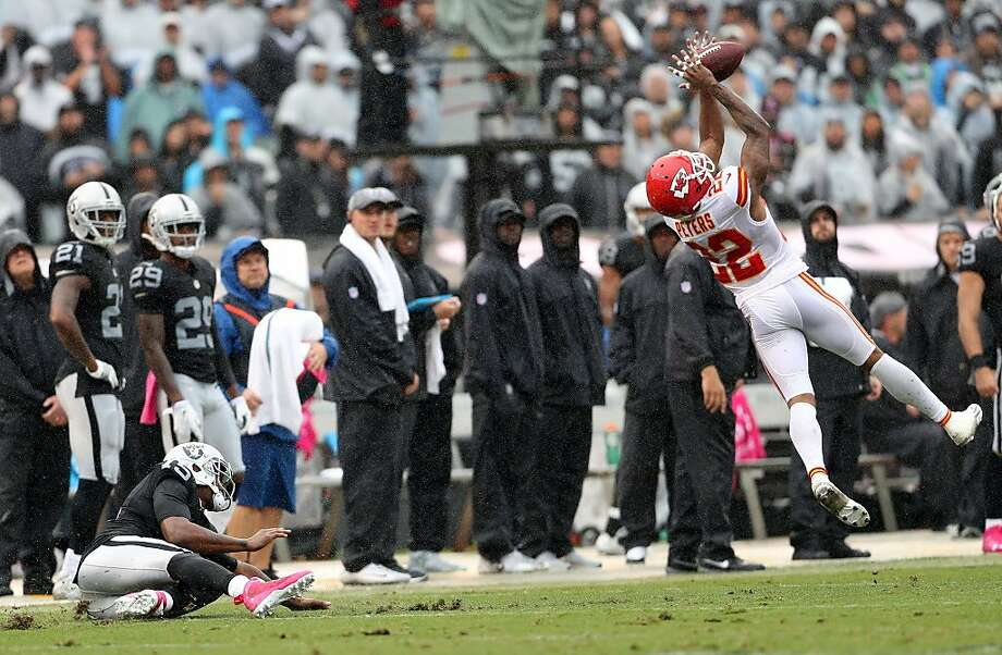 Kansas City Chiefs' Marcus Peters intercepts a 1st quarter pass after Oakland Raiders' Michael Crabtree slipped on the wet turf during Raiders' 26-10 loss during NFL game at Oakland Coliseum in Oakland, Calif., on Sunday, October 16, 2016. Photo: Scott Strazzante, The Chronicle