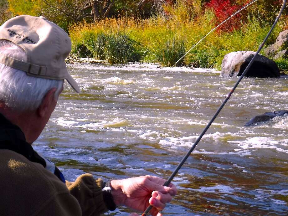 Bob Simms deals with a big Klamath River rainbow trout, his rod arcing deeply under full pressure, on a raft trip on the little-known Keno section of the Upper Klamath. Photo: Tom Stienstra, Tom Stienstra / The Chronicle