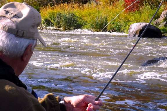 Bob Simms battles a big Klamath River rainbow trout, his rod arcing deeply under full pressure, on a raft trip on the little-known Keno section of the Upper Klamath