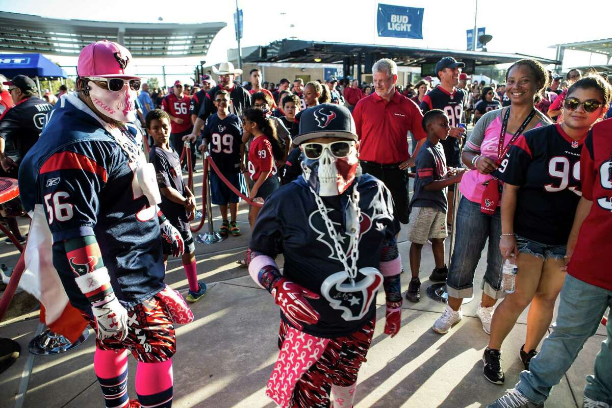 Houston Texans fans walk outside NRG Stadium as they arrive for an NFL football game between the Texans and the Indianapolis Colts on Sunday, Oct. 16, 2016, in Houston.