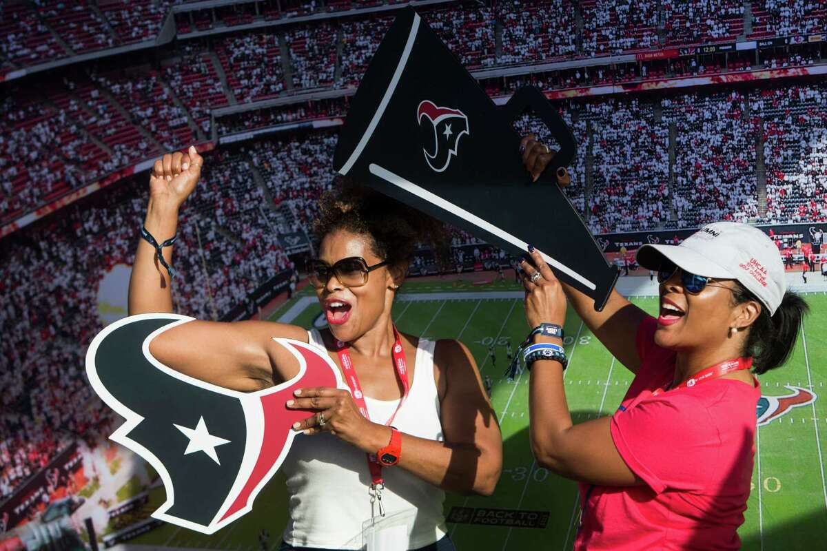 Houston Texans fans Ann Green and Tracy Venice cheer as the pose for a photo before an NFL football game between the Texans and the Indianapolis Colts at NRG Stadium on Sunday, Oct. 16, 2016, in Houston.