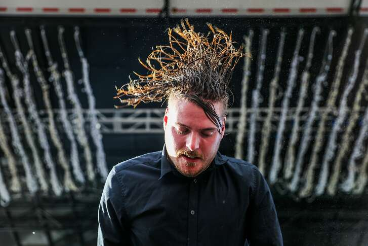 George Clarke of Deafheaven flips his hair while performing on the second day of the Treasure Island Music Festival in San Francisco, California, on Sunday, Oct. 16, 2016.