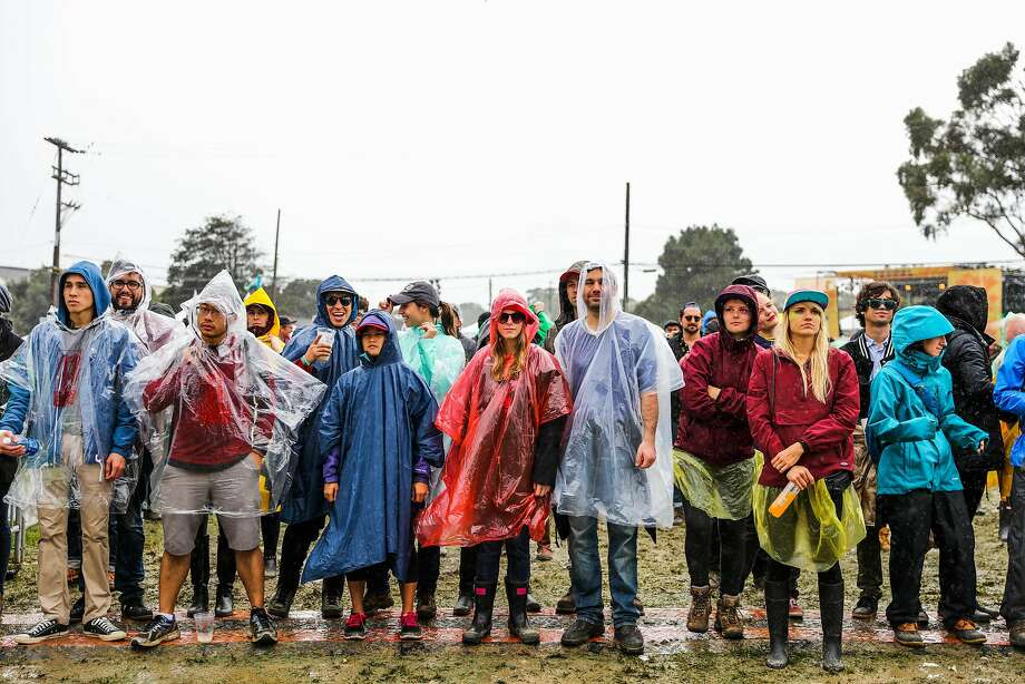 People wear ponchos in the rain as they listen to Christine and The Queens perform at the second day of the Treasure Island Music Festival in San Francisco, California, on Sunday, Oct. 16, 2016. Photo: Gabrielle Lurie, The Chronicle
