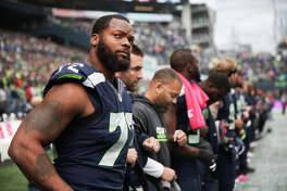 Seahawks defensive lineman Michael Bennett stands in line with the majority of his team during the national anthem before playing the Atlanta Falcons at CenturyLink Field, Sunday, Oct. 16, 2016.