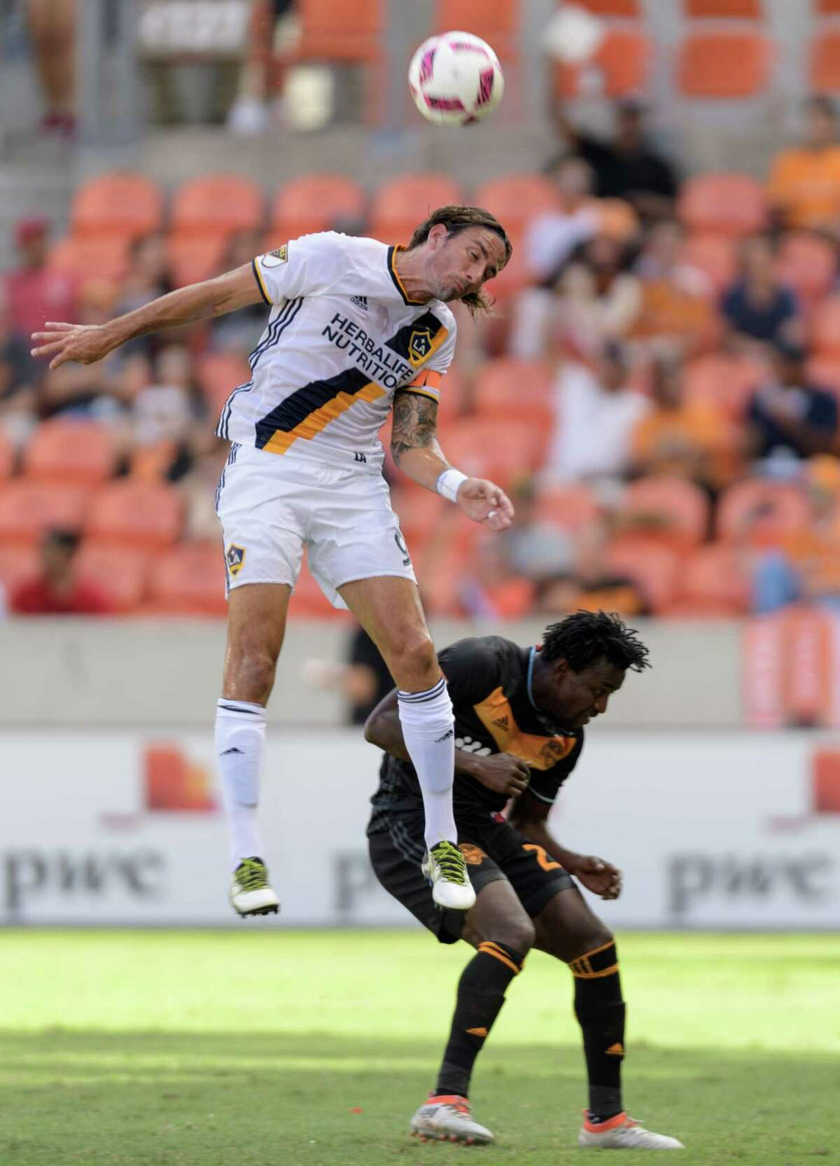 Alan Gordon (9) of the LA Galaxy wins a header over Abdoulie Mansally (20) of the Houston Dynamo in the first half in an MLS game on Sunday, October 16, 2016 at BBVA Compass Stadium in Houston Texas.