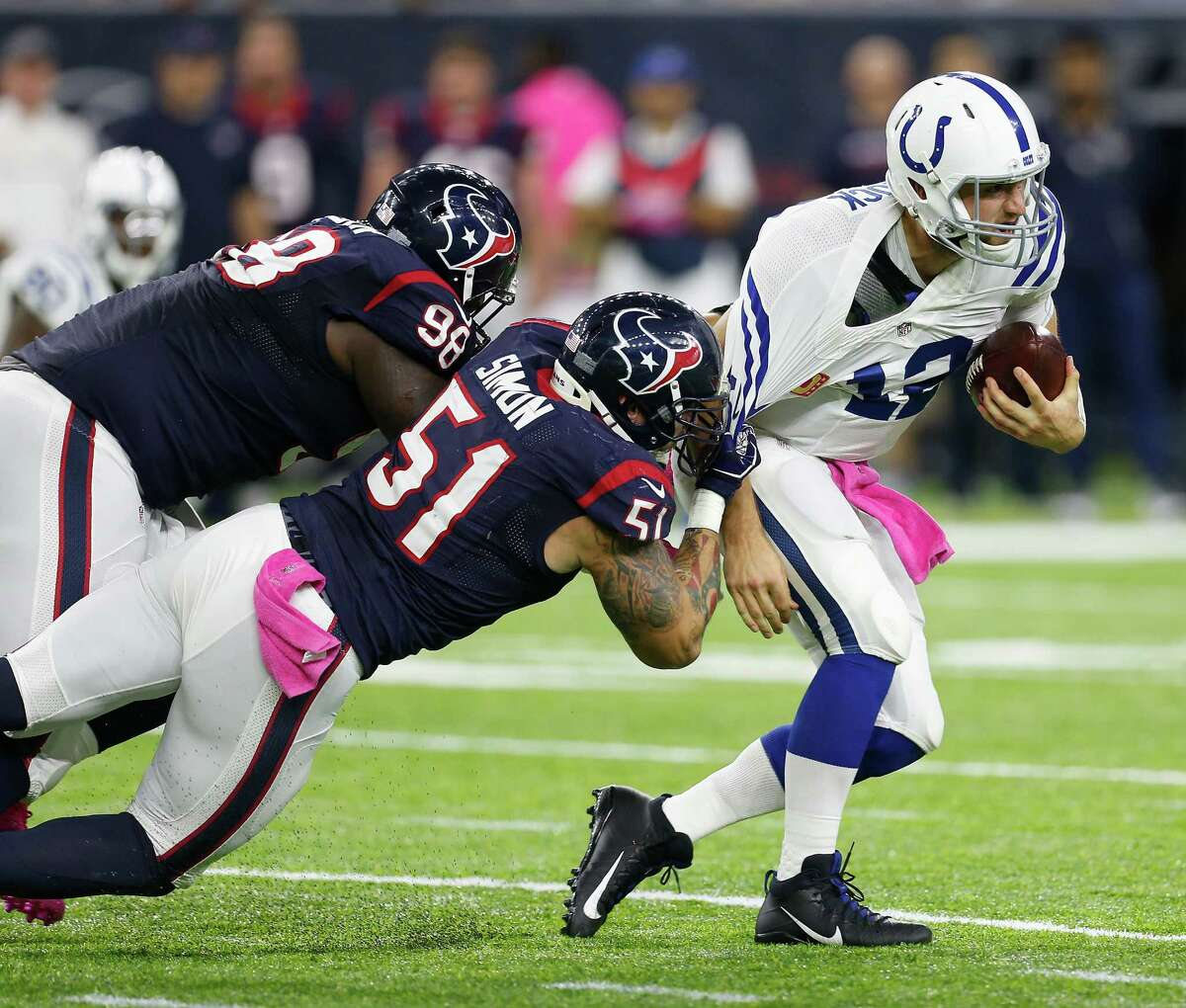 Indianapolis Colts quarterback Andrew Luck (12) is sacked by Houston Texans outside linebacker John Simon (51) and nose tackle D.J. Reader (98) during the first quarter of an NFL football game at NRG Stadium on Sunday, Oct. 16, 2016, in Houston.