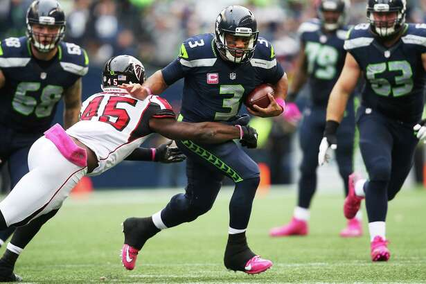 Seahawks quarterback Russell Wilson breaks through a tackle attempt by Falcons linebacker Deion Jones during the second half of Seattle's game against Atlanta, Sunday Oct. 16, 2016, at CenturyLink Field.