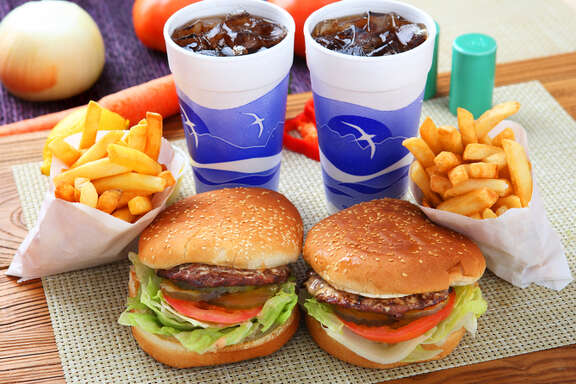 Two hamburgers, two sodas, and two orders of fries are pictured.