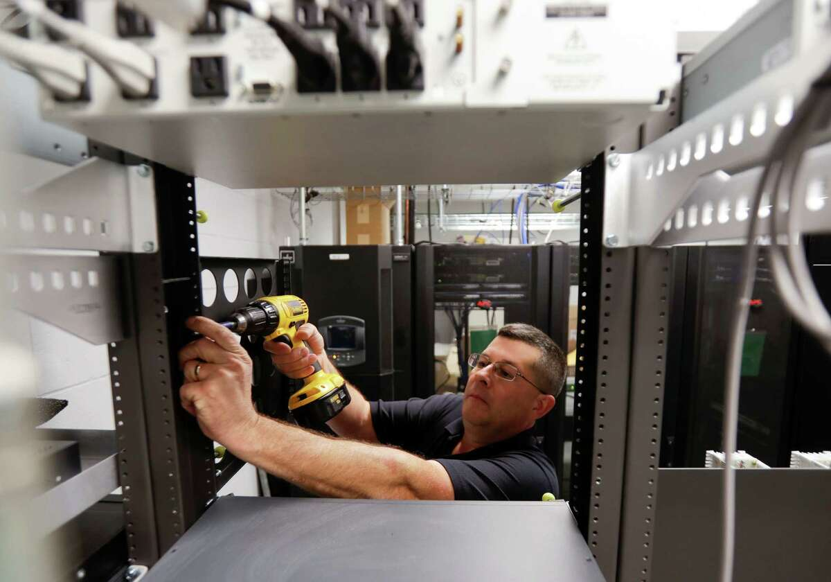 In this Thursday, Oct. 13, 2016 photo, Robert Mohan installs new radio equipment at the 911 dispatch center at the Rensselaer County Public Safety Building in Troy, N.Y. New York trails other states in modernizing its 911 systems to handle greater cellphone use, in part because lawmakers routinely divert money intended for that purpose and use it to plug holes in the state budget. (AP Photo/Mike Groll) ORG XMIT: NYMG304