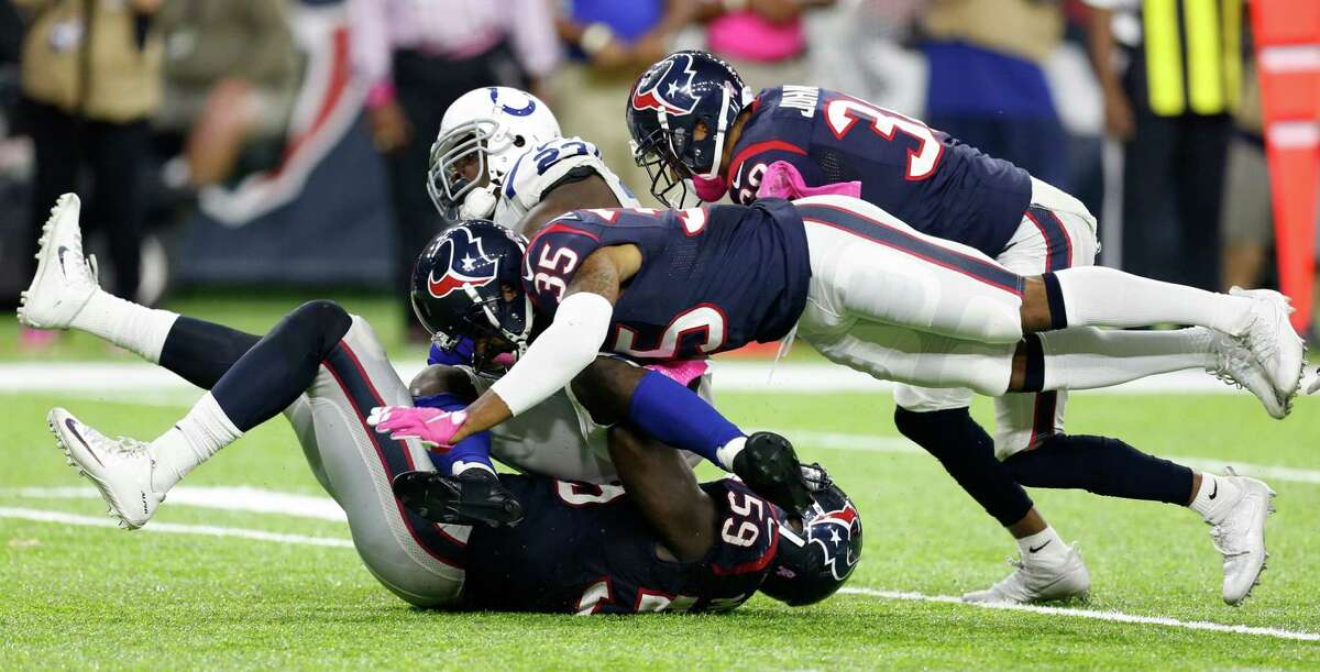 Houston Texans outside linebacker Whitney Mercilus (59) and Houston Texans defensive back Eddie Pleasant (35) stop Indianapolis Colts running back Frank Gore (23) for a loss during the fourth quarter of an NFL football game at NRG Stadium on Sunday, Oct. 16, 2016, in Houston.