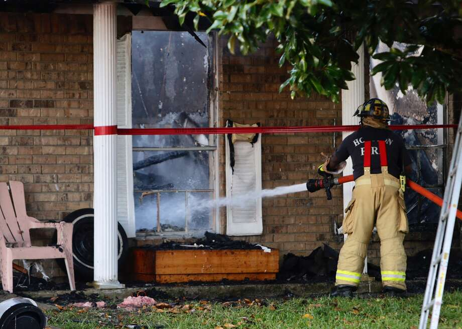 Firefighters continue to put out hot spots on a house fire on Marinewood Drive in southwest Houston Monday, October 17, 2016. (Mark Mulligan / Houston Chronicle)