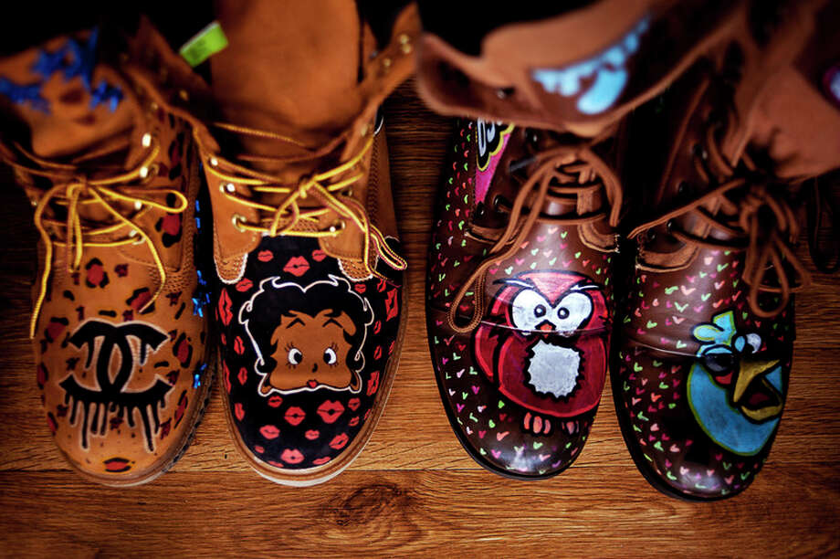 ERIN KIRKLAND   ekirkland@mdn.net A selection of acrylic-painted boots made by Midland resident Sheldon Edwards sit out on Wednesday in Midland. Edwards has started collaborating with fellow Midland resident Tim Holmes, who screen prints clothes. Holmes' clothing company is titled Inspired Individual, while Edwards' is known as Captain Shel. / Midland Daily News