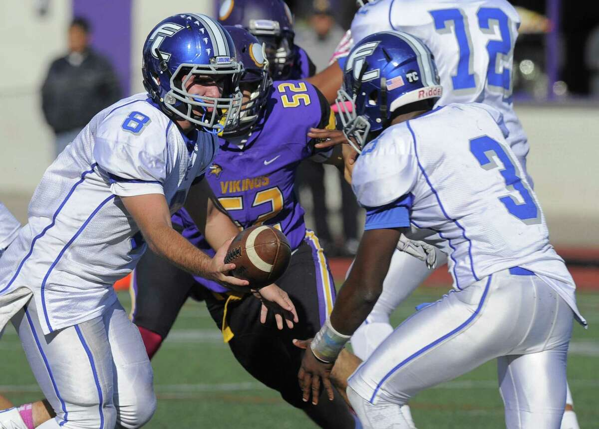 Ludlowe quarterback Josh Evans hands off to Javion Beasley (3) during action on Saturday against Westhill in Stamford. The Falcons dropped a 21-0 decision.