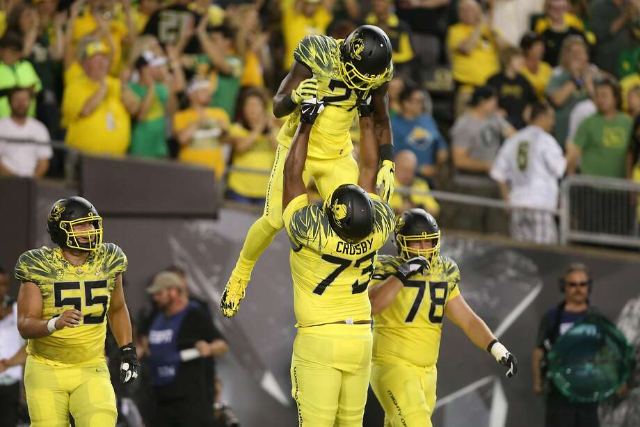 Oregon's Royce Freeman, center, is hoisted in the air by teammate Tyrell Crosby after scoring a touchdown against Virginia during the first quarter of an NCAA college football game Saturday, Sept. 10, 2016 in Eugene, Ore. (AP Photo/Chris Pietsch) Photo: Chris Pietsch, Associated Press