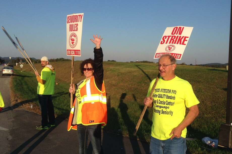 Workers hold picket signs outside the Jim Beam plant in Clermont, Ky., on Saturday. More than 200 union workers walked off their jobs at Beam distilleries at Clermont and Boston in Kentucky after voting Friday to reject the latest contract offer from the world's leading bourbon producer. Photo: Bruce Schreiner /Associated Press / ap