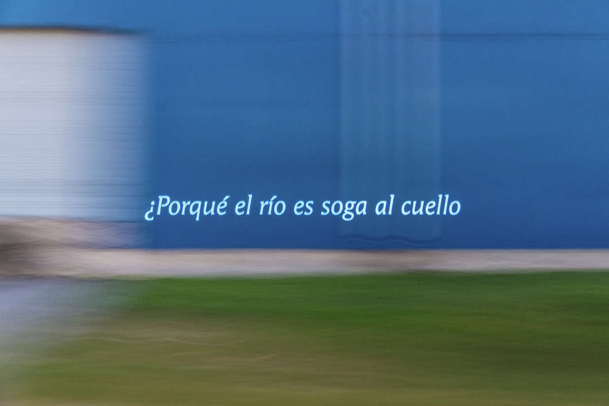 """An image from a rehearsal run for Pablo Gimenez-Zapiolas' roving """"Eastext"""" projection performance. This one shows a line text from a poem by Vanessa Torres., """"Porque el río es soga al cuello,"""" which translates as, """"Why the river is rope around the neck."""""""