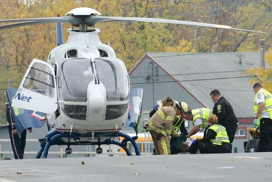 Paramedics work on Freemans Bridge Road as a helicopter prepares to flight a patient to the hospital on Monday. (Skip Dickstein / Times Union)