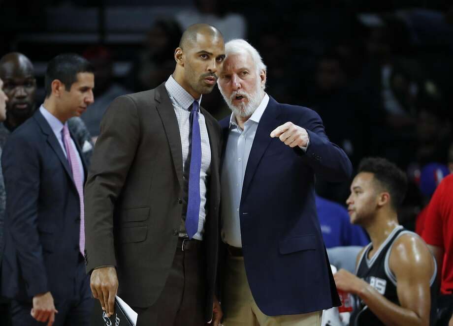 San Antonio Spurs head coach Gregg Popovich, right, talks with assistant Ime Udoka against the Detroit Pistons in the first half of a preseason NBA basketball game in Auburn Hills, Mich., Monday, Oct. 10, 2016. (AP Photo/Paul Sancya) Photo: Paul Sancya, Associated Press