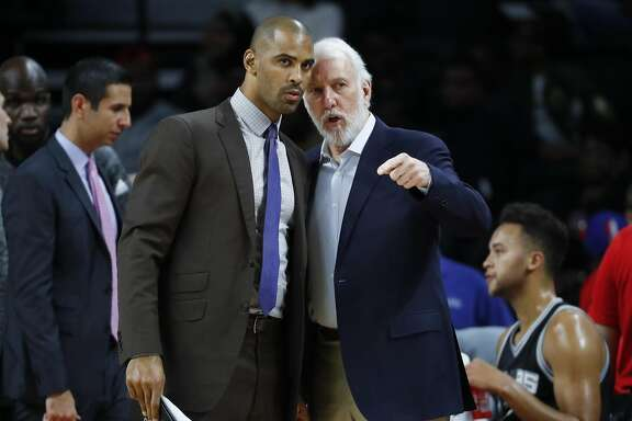 San Antonio Spurs head coach Gregg Popovich, right, talks with assistant Ime Udoka against the Detroit Pistons in the first half of a preseason NBA basketball game in Auburn Hills, Mich., Monday, Oct. 10, 2016. (AP Photo/Paul Sancya)