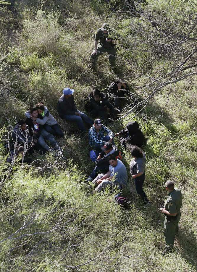 With the support of a U.S. Customs and Border Protection Air and Marine Operations Bell Huey, Border Patrol agents capture a group illegal immigrant hiding in brush on a ranch northeast of Rio Grande City, Texas, Tuesday, Oct. 4, 2016. Photo: JERRY LARA, Staff / San Antonio Express-News / © 2016 San Antonio Express-News