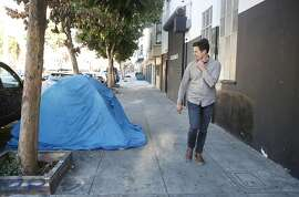 Carl Petersen, architect, walks past a tent along 15th Street, on Wednesday, October 12,  2016 in San Francisco,  California.