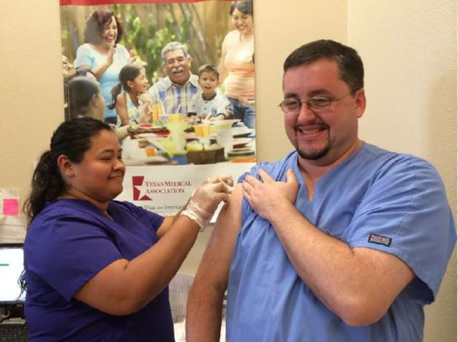 Maria Aguilera, medical assistant at SAI Primary Care, gives a flu shot to David Pearson during a Sept. 10 health fair  in Manvel. Pearson, a volunteer at the health fair, was among 115 people that received free flu shots. Shots are available at some local clincs, and health officials advise residents to get them early in the flu season.