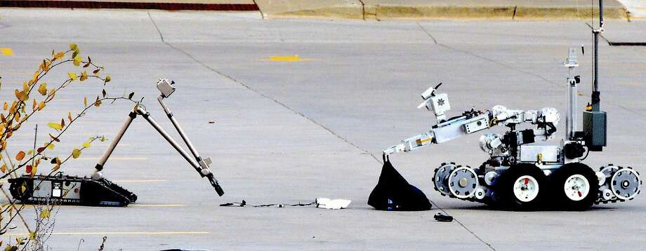 In this Oct. 11 photo provided by The Mountain-Ear, a bomb retrieval unit works near the police station in Nederland, Colo., after a homemade explosive was found outside the station located in a strip mall in the small town. Photo: Barbara Lawlor, Associated Press