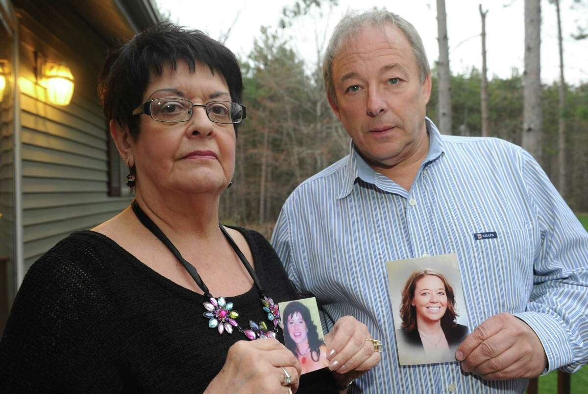 Martha Lasher-Warner and Bill Hart hold photographs of their daughters,who where both killed in domestic violence attacks, on Thursday April 18, 2013 in East Greenbush, N.Y. (Michael P. Farrell/Times Union)