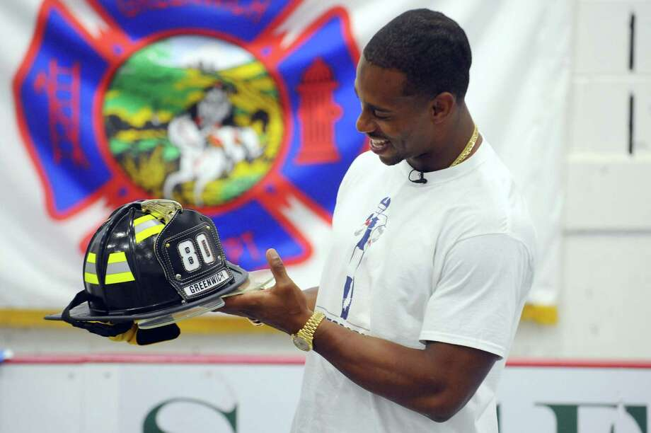 New York Giants wide receiver Victor Cruz smiles after receiving an honorary Greenwich fire helmet given to him by Greenwich Deputy Fire Marshal Chris Moynahan during an event focused on fire safety at the Boys and Girls Club in Greenwich, Conn. on Monday, Oct. 17, 2016. Photo: Michael Cummo / Hearst Connecticut Media / Stamford Advocate