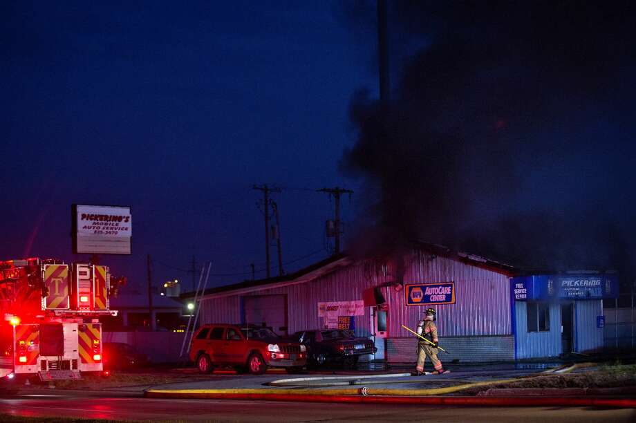 Midland firefighters work to put out a blaze at Pickering Automotive Services at 402 East Lyon Road on Monday night. Photo: Nick King/Midland  Daily News/Nick King