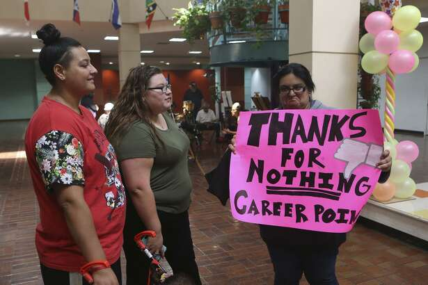 """Anissa Campos (right) holds a sign expressing her disappointment with Career Point College Monday October 17, 2016 after the for-profit school shut its doors. A letter sent to students and teachers from its president and CEO said the school is shutting its doors after management discovered that three long-term employees had """"collaborated to violate the rules related to student aid funds."""" Campos was studying to be a medical assistant."""