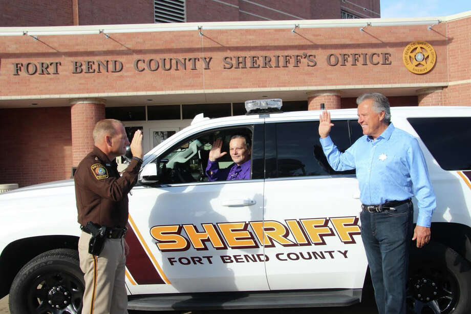 """Fort Bend County Sheriff Nehls, left, deputizes Donny Farmer, operating the many facets of the patrol car and, Michael Wilhelm. Farmer and Wilhelm both are Hope for Three volunteers who won their """"Life as Sheriff"""" law enforcement roles after being high bidders at an auction to benefit the nonprofit that bridges the gap between families and providers of services needed to help children on the autism spectrum. Photo: Brenda Perry"""