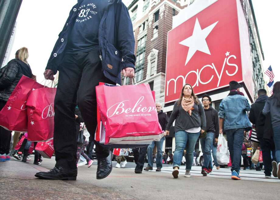 FILE - In this Friday, Nov. 27, 2015, file photo, shoppers carry bags as they cross a pedestrian walkway near Macy's in Herald Square,  in New York. Macy's announced Monday, Oct. 17, 2016, it is staying committed to Thanksgiving Day shopping, confirming that it will open an hour earlier on Thanksgiving Day. The move comes as several stores and a mall operator have decided to close for the turkey feast. (AP Photo/Bebeto Matthews, File) ORG XMIT: NYBZ108 Photo: Bebeto Matthews / Copyright 2016 The Associated Press. All rights reserved.