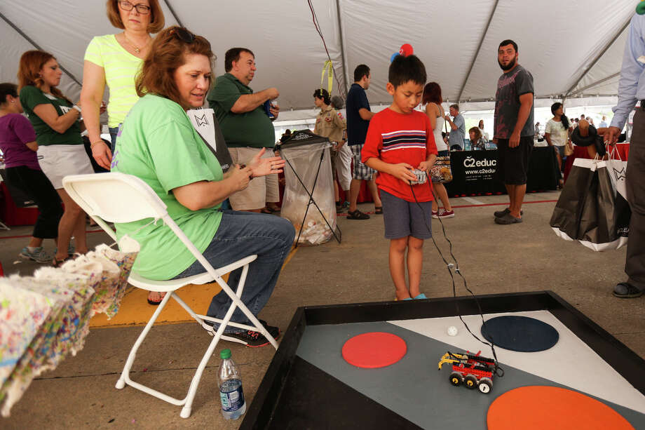 John Wu, 8, tries a demo for the Early Robotics Program at The Woodlands Children's Museum, as Rhonda Sheldon, a science teacher with the museum, looks on during the Taste of the Village event on Saturday, Oct. 15, 2016, in the H-E-B parking lot on the Woodlands Parkway and Kuykendahl Road. Photo: Michael Minasi, Staff / © 2016 Houston Chronicle