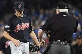 Cleveland Indians starting pitcher Trevor Bauer looks at his bleeding finger during first inning of game three American League Championship Series baseball action against the Toronto Blue Jays in Toronto on Monday, Oct. 17, 2016. (Nathan Denette/The Canadian Press via AP)