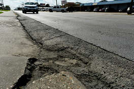 Motorists drive past a section of rough pavement on Nederland Avenue on Monday. The City of Nederland is proposing a complete overhaul of the street between Twin City Highway and U.S. 69.  Photo taken Monday 10/17/16 Ryan Pelham/The Enterprise