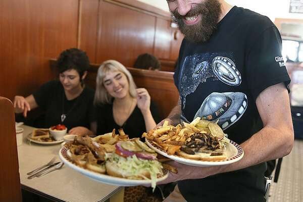 Soda jerk Matt Marshall (right) serves plates to Whitney Rescino (back left) and Erika Garcia (back middle) at St. Francis Fountain in the Mission on Monday, October 17, 2016, in San Francisco, Calif.