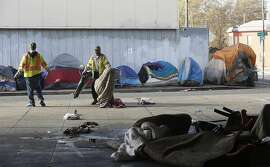 City workers do a sweep at the homeless encampment on 35th and Magnolia Streets in West Oakland as the city promise to deliver porter potties, fences, regular trash pickup, and counseling to about 45 people  on Monday, October 17, 2016, in Oakland, Calif.